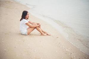 jonge vrouw zittend op het strand foto