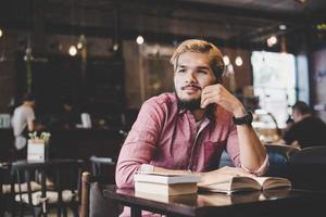 jonge bebaarde hipster lezen van een boek in een café foto