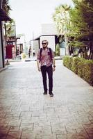 portret van een knappe hipster man in spijkerbroek en zonnebril lopen