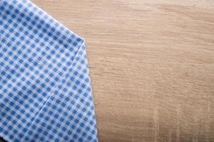 geruit blauw servet op een houten achtergrond foto