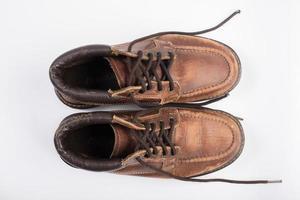paar oude bruine laarzen geïsoleerd op een witte achtergrond foto