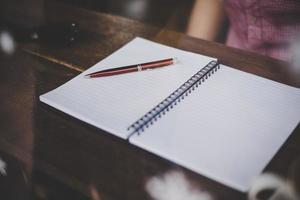 klein notitieblok met pen op houten tafel met raam reflectie foto