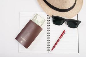 paspoorten, hoed, camera, bril en pen op een papieren vloer klaar om te reizen