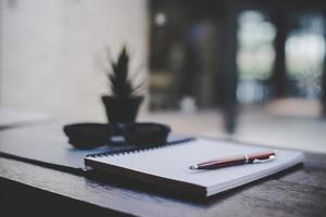 klein notitieblok met een pen op hout achtergrond in een café foto