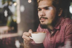jonge man zit in een café en een kopje koffie drinken foto