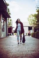 portret van jonge stijlvolle hipster vrouw lopen op straat, glimlachend geniet van weekends. vintage van hipster tiener met tas in de hand. foto