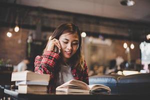 hipster tiener zitten en genieten van een boek in een café foto