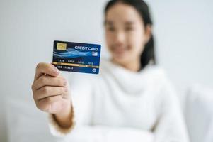 jonge vrouw met een creditcard lachend op bed