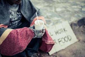 dakloze man gewikkeld in doek en noedels eten foto