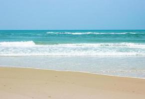 oceaangolven op strand met heldere blauwe hemel