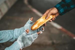 een broodbakmachine geeft aan een bedelaar