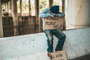 bedelaar zit op een slagboom met daklozen, help alstublieft ondertekenen foto
