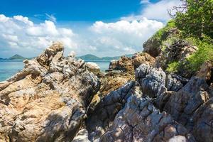 tropisch eilandrots op het strand met bewolkte blauwe hemel foto