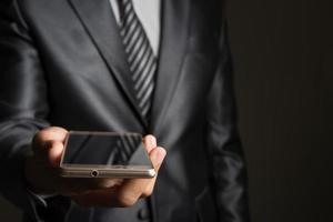 portret van zakenman met smartphone tegen zwarte achtergrond