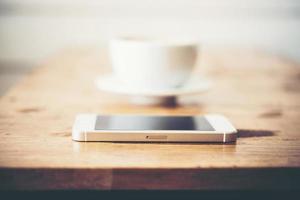 een kopje koffie en smartphone op houten tafel in café foto