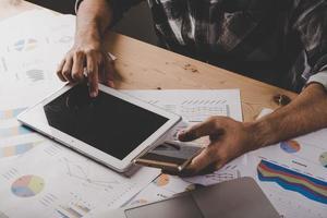 zakenman werken met een leeg scherm digitale tablet en laptop op houten bureau in kantoor foto