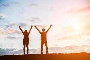 silhouet van gelukkige jonge paar samen tegen de prachtige zonsondergang foto