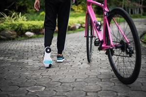 close-up van achterzijde van vrouw met racefiets in het park foto