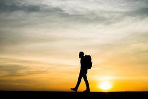 silhouet van een jonge backpackermens die tijdens zonsondergang loopt foto
