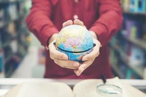 jonge student aarde model in de hand te houden