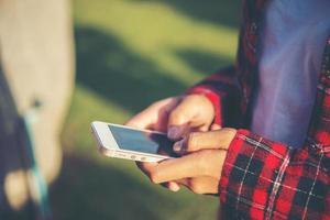 jonge vrouw met behulp van een smartphone buiten in een park foto