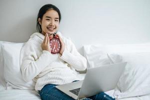 jonge vrouw zittend op haar bed met een wekker