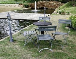 tafel en stoelen bij vijver