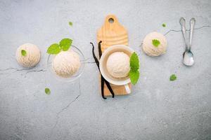 vanille-ijssmaak in kom met vanillestokjes op concrete achtergrond foto