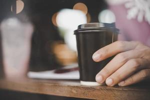 close-up van jonge man met koffie om mee te nemen in café