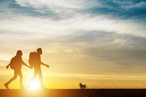 silhouet van paar wandelen tijdens zonsondergang