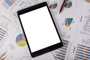 tablet met leeg scherm over zakelijke grafieken