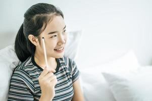 een vrouw die met een glimlach zit te denken en een potlood vasthoudt foto