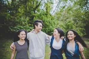 gelukkige jeugdvrienden die buiten glimlachen in een park foto