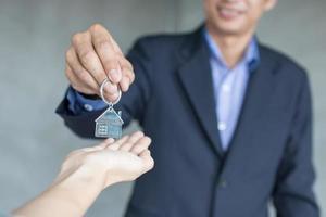 makelaar en onroerend goed nemen de sleutel tot vastgoedeigenaren foto