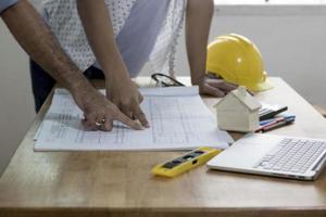 ingenieurs bespreken en plannen op werktafel foto