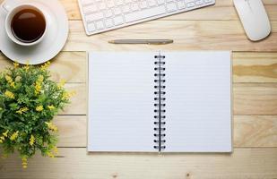 bovenaanzicht van bureau met notitieboekje en koffie foto