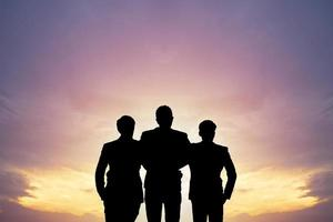 drie mensen silhouet in de zonsondergang foto