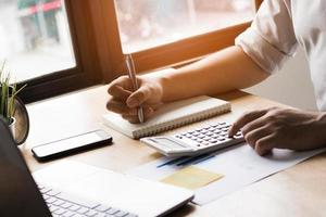persoon die in een dagboek schrijft en een rekenmachine gebruikt foto