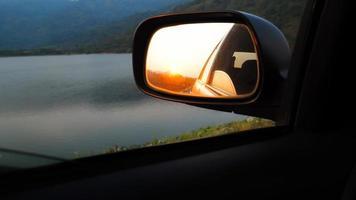 zonsondergang in achteruitkijkspiegel foto