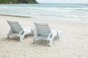 witte ligbedden op het strand foto