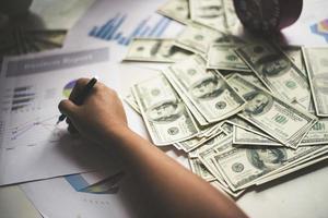 zakenman met documentgrafiek en usd geld op achtergrond
