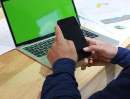 man met een telefoon in de buurt van een laptopmodel foto