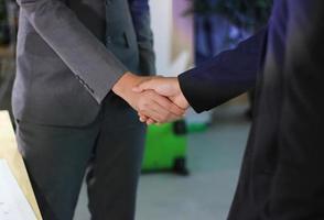 twee zakelijke professionals handen schudden in kantoor foto