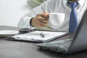 persoon in een stropdas met een kopje koffie foto