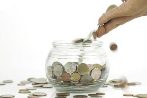 hand geld steken in een pot foto