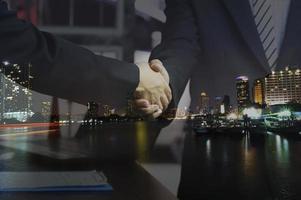 mannen schudden handen met stad achtergrond foto