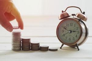 hand geld op een stapel munten te zetten