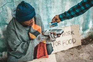 persoon geeft aan een bedelaar aan de kant van de weg