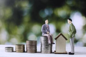 zakenmensen model met geldmunten en huis foto