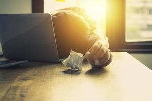persoon liggend met hoofd op bureau en verfrommeld wit papier
